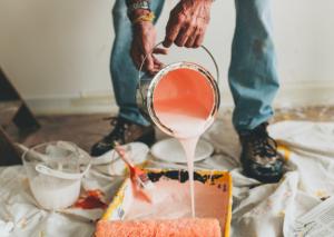 Ouvrier en train de verser un pot de peinture rose dans un bac de peinture