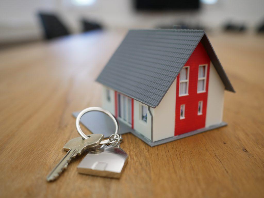 Trousseau de clés posé sur une table en bois à côté d'une maison miniature rouge, blanche et grise