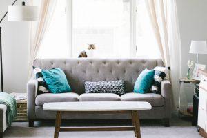 salon avec canapé gris table base blanche coussins à motifs et bleus unis avec un chat sur le canapé