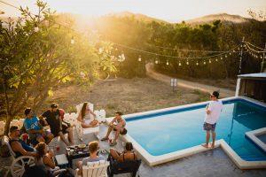 extérieur de maison avec piscine et guirlande lumineuse avec des personnes assises qui prennent un verre