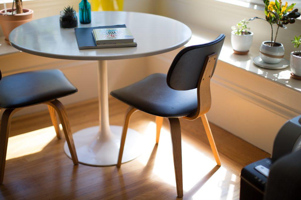 Salle à manger avec une table ronde en verre et deux sièges noirs disposés dans l'angle d'une pièce ensoleillée