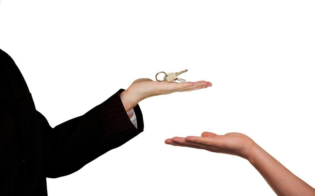 Un agent immobilier qui donne des clés à un locataire