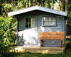abri de jardin sous des arbres avec banc devant