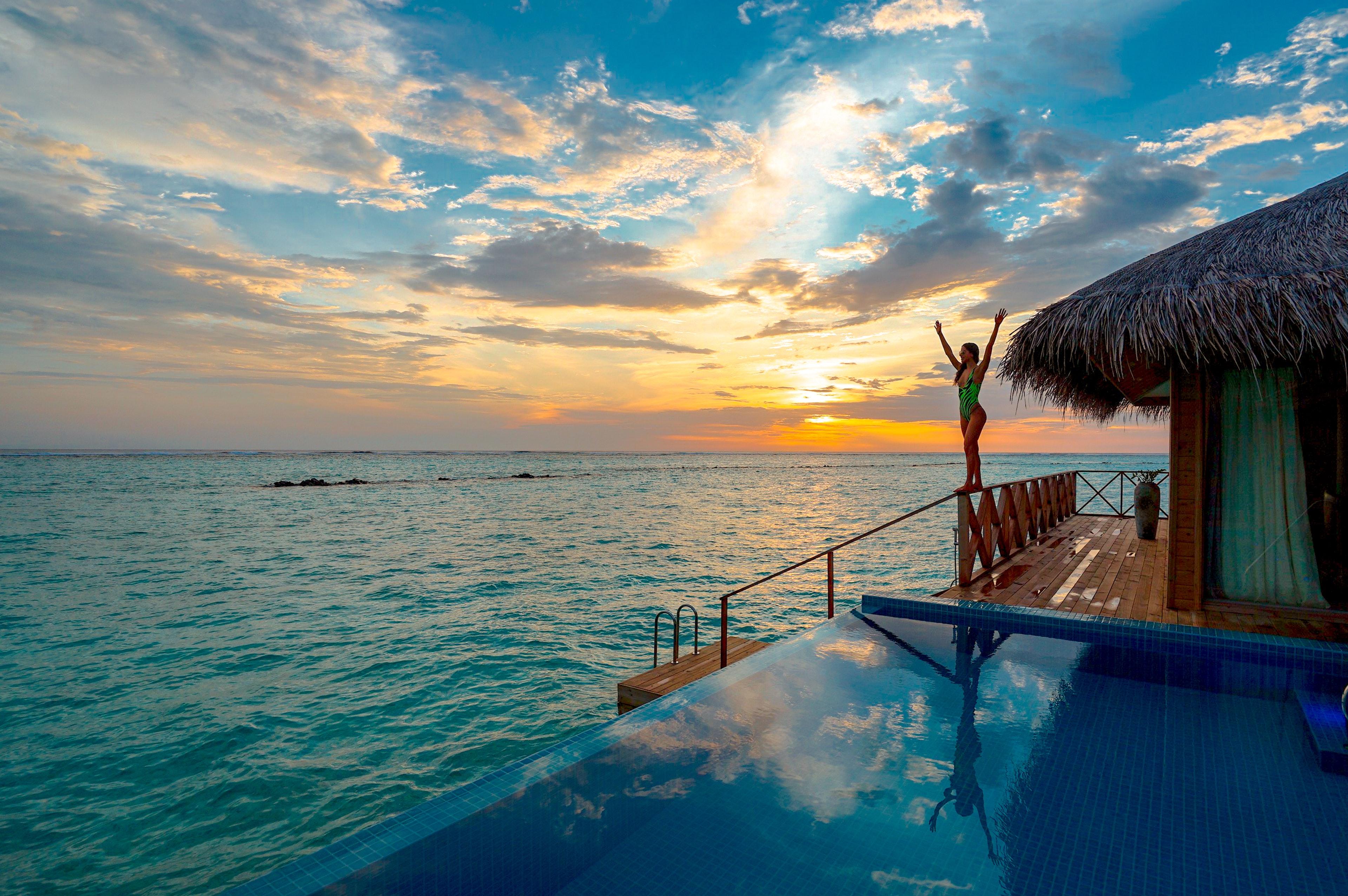 Jeune femme au bord de la piscine dans sa villa tropicale