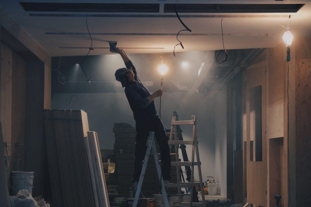 ouvrier dans une maison sur un escabeau